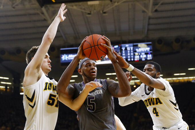 Northwestern center Dererk Pardon, center, grabs a rebound between Iowa's Nicholas Baer, left, and Isaiah Moss, right, during the first half of an NCAA college basketball game, Sunday, Feb. 10, 2019, in Iowa City, Iowa. (AP Photo/Charlie Neibergall)