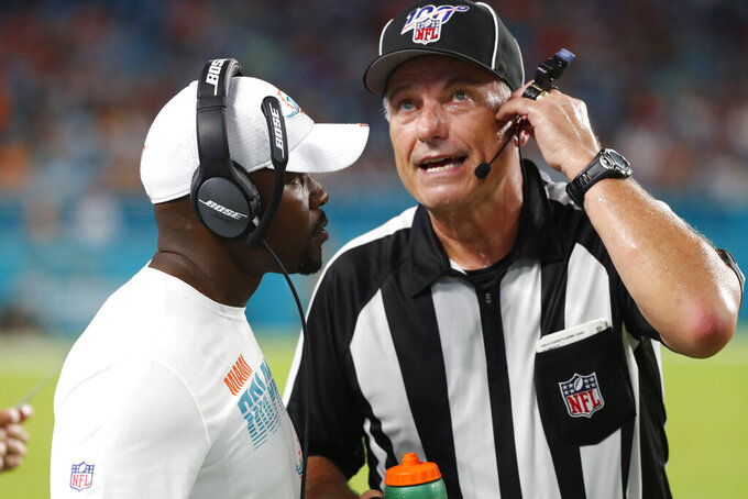 Miami Dolphins coach Brian Flores, left, talks with official Mike Weatherford during the first half of a preseason NFL football game against the Atlanta Falcons, Thursday, Aug. 8, 2019, in Miami Gardens, Fla. (AP Photo/Wilfredo Lee)