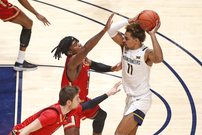West Virginia forward Derek Culver (1) is defended by Northeastern guard Jahmyl Telfort (11), rear, and forward Coleman Stucke (15) during the first half of an NCAA college basketball game Tuesday, Dec. 29, 2020, in Morgantown, W.Va. (AP Photo/Kathleen Batten)