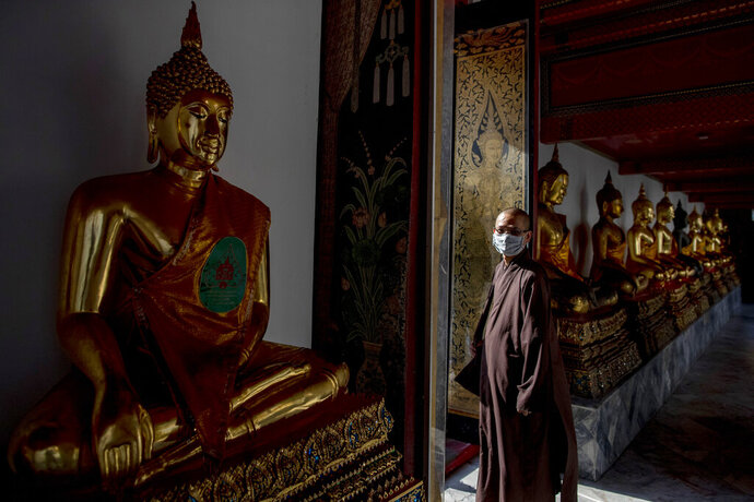 In this Feb. 13, 2020, photo, a Buddhist monk from Vietnam wearing a face mask walks amid Buddhist statues at Wat Pho in Bangkok, Thailand. There were less crowds in Bangkok's popular Wat Pho, a centuries-old Buddhist temple known for its giant reclining buddha, due to the virus scare. The complex of temples is normally visited by thousands of tourists. (AP Photo/Gemunu Amarasinghe)