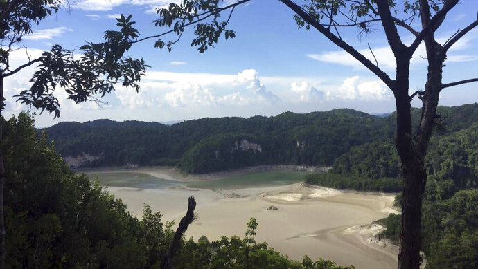 In this photo provided by Mexico's National Commission for Protected Nature Areas, the diminishing waters of the Metzabok Lagoon are seen amidst its drying lake bed, in the Lacandon jungle of Chiapas State in southern Mexico, in the first half of August, 2019. During the month of August, the Metzabok lake, which normally covers 220 acres (89 hectares), dried up completely, leaving cracked mud where the surrounding jungle used to reflect in the translucent waters and Lacandon Indians traveled by canoe. (CONANP via AP)