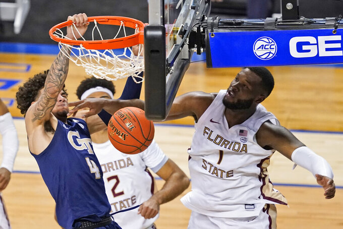 Georgia Tech guard Jordan Usher (4) dunks in front of Florida State forward RaiQuan Gray (1) during the second half of an NCAA college basketball Championship game of the Atlantic Coast Conference tournament in Greensboro, N.C., Saturday, March 13, 2021. (AP Photo/Gerry Broome)