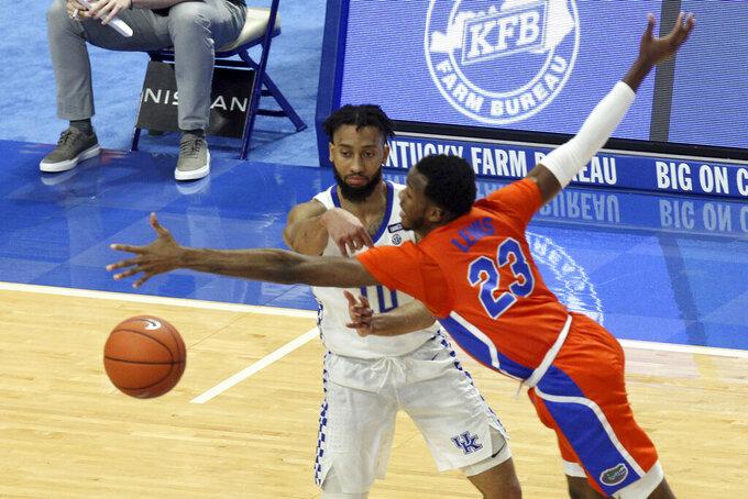 Kentucky's Davion Mintz, left, passes around Florida's Scottie Lewis (23) during the second half of an NCAA college basketball game in Lexington, Ky., Saturday, Feb. 27, 2021. (AP Photo/James Crisp)