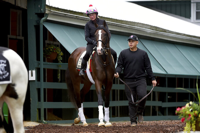 Preakness contender War of Will, with exercise rider Kim Carroll aboard, is led out of the barn, Tuesday, May 14, 2019, at Pimlico Race Course in Baltimore. The Preakness Stakes horse race is scheduled to take place Saturday, May 18. (AP Photo/Will Newton)