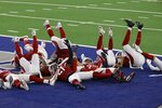 Members of the Arizona Cardinals defense act out a bowling pin strike dramatization after being hit by a ball rolled by Byron Murphy Jr. who intercepted a Dallas Cowboys quarterback Andy Dalton pass in the second half of an NFL football game in Arlington, Texas, Monday, Oct. 19, 2020. (AP Photo/Ron Jenkins)
