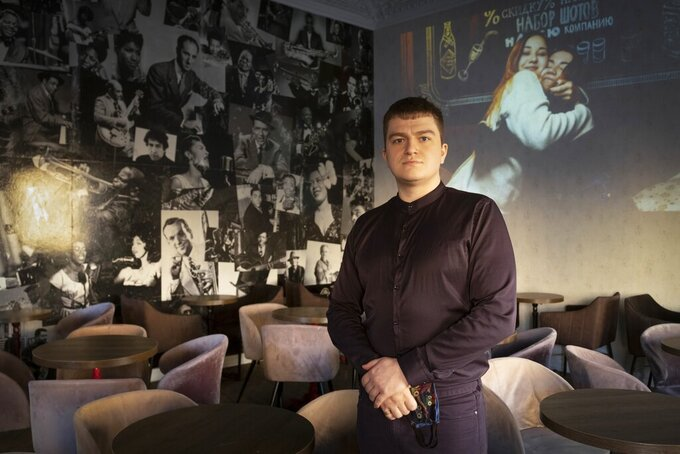 Mikhail Kavin, manager of the Commode bar in St. Petersburg, Russia, poses for a photo prior to his interview with The Associated Press on Wednesday, March 24, 2021. Police raided the bar in December for serving customers behind closed doors past 11 p.m. in violation of coronavirus restrictions. Even with flouting the rules, the bar hasn't bounced back to its pre-pandemic level of sales, Kavin said. (AP Photo/Dmitri Lovetsky)