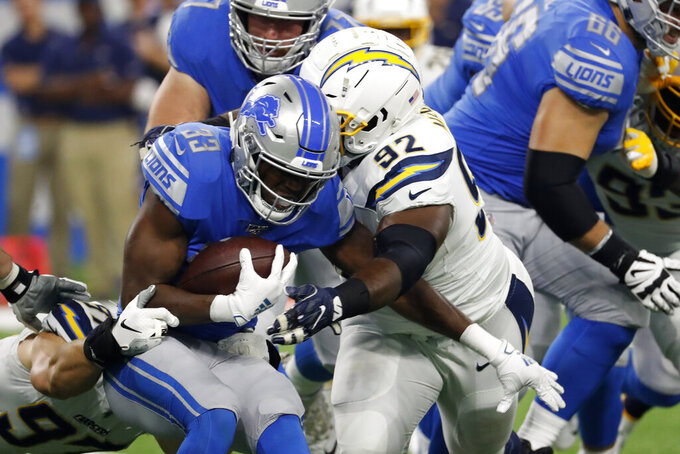 Detroit Lions running back Kerryon Johnson (33) is stopped by Los Angeles Chargers defensive tackle Brandon Mebane (92) in the first half of an NFL football game in Detroit, Sunday, Sept. 15, 2019. (AP Photo/Rick Osentoski)