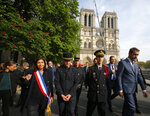 French Interior Minister Christophe Castaner, right, Paris mayor Anne Hidalgo, left, and other officials Paris walk by Notre Dame cathedral Thursday, April 18, 2019 in Paris. France paid a daylong tribute Thursday to the Paris firefighters who saved Notre Dame Cathedral from collapse, while construction workers rushed to secure an area above one of the church's famed rose-shaped windows and other vulnerable sections of the fire-damaged landmark. (AP Photo/Michel Euler, Pool)