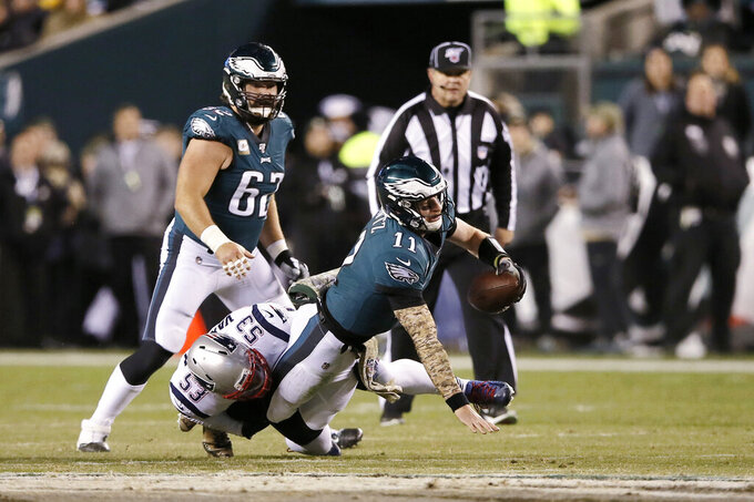 Philadelphia Eagles' Carson Wentz (11) is tackled by New England Patriots' Kyle Van Noy (53) during the first half of an NFL football game, Sunday, Nov. 17, 2019, in Philadelphia. (AP Photo/Michael Perez)