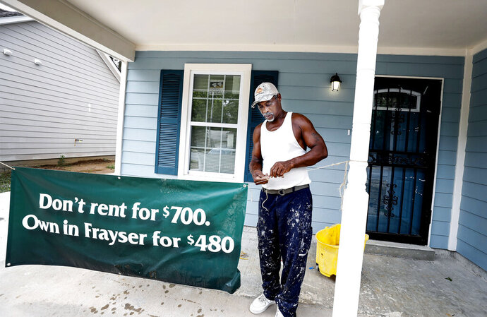 Contractor Ronnie Crawford hangs a sign outside a newly built home in Frayser, Tenn. Wednesday, July 17, 2019. (Mark Weber/Daily Memphian via AP)