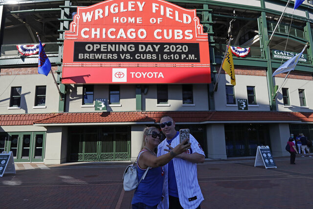 Sandra Bilger, left, and Dustin Moore take a photo in front of the marquee at Wrigley Field before an opening day baseball game between the Chicago Cubs and the Milwaukee Brewers in Chicago, Friday, July 24, 2020, in Chicago. In a normal year, that would mean a sellout crowd at Wrigley Field and jammed bars surrounding the famed ballpark but in a pandemic-shortened season, it figures to be a different atmosphere. (AP Photo/Nam Y. Huh)