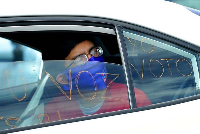 A man looks out of a car window as he takes part in a car rally Thursday, Aug. 13, 2020, at the Capitol in Phoenix. A coalition of voting rights groups in Arizona have banded together with a lofty goal of getting one million people to vote this November. (AP Photo/Matt York)