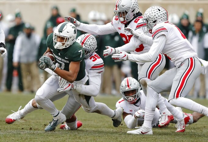 Michigan State wide receiver Cody White (7) is stopped by Ohio State linebacker Malik Harrison (39) during the first half of an NCAA college football game, Saturday, Nov. 10, 2018, in East Lansing, Mich. (AP Photo/Carlos Osorio)