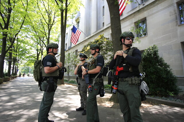Federal officers stand outside the Department of Justice as Attorney General William Barr speaks during a virtual press conference inside the building Thursday, June 4, 2020, in Washington. (AP Photo/Manuel Balce Ceneta)