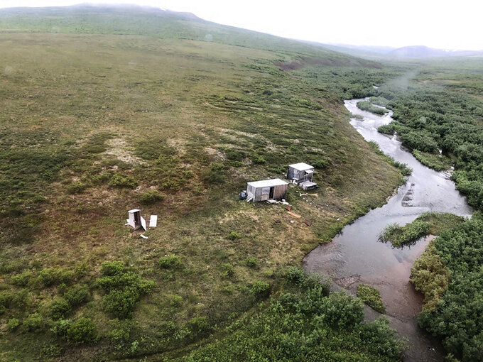 This photo provided by the U.S. Coast Guard District 17 shows a remote mining camp near Nome, Alaska, where a Coast Guard Air Station Kodiak aircrew rescued a survivor of a bear attack, on July 16, 2021. A miner who said he was harassed by a bear for seven straight nights in the tundra near Nome was rescued when a passing Coast Guard helicopter spotted the SOS, an internationally recognized sign for help, on top of his cabin. (U.S. Coast Guard via AP)