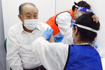 An elderly man receives a shot of the Pfizer's COVID-19 vaccine in Nagoya, Aichi prefecture, central Japan on April 14, 2021. Japan is set to raise the coronavirus alert level in Tokyo's three neighboring prefectures and Aichi prefecture to allow tougher measures as a more contagious coronavirus variant spreads and doubts are growing whether the Olympics can go ahead. The move comes only four days after the government placed Tokyo on alert while the vaccination campaign has left less than 1% of the population inoculated. (Kyodo News via AP)