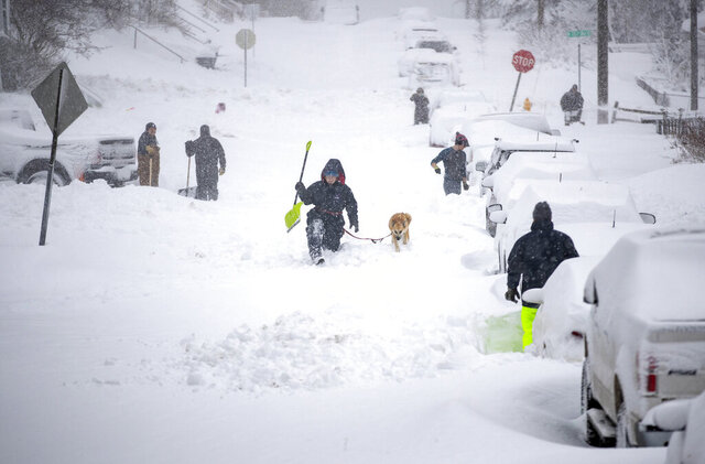 Neighbors work together in an effort to clear out as much snow as possible from E. 8th Street, Sunday, Dec. 1, 2019, in Duluth, Minn. (Alex Kormann/Star Tribune via AP)
