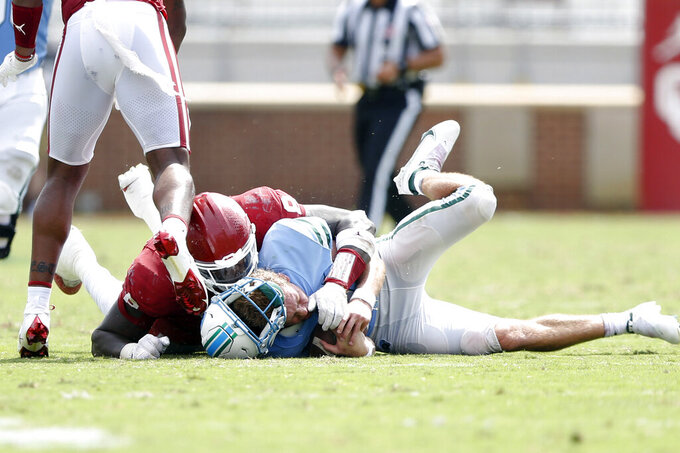 Oklahoma defensive lineman Perrion Winfrey (8) tackles Tulane quarterback Michael Pratt (7) short of the first down marker on fourth down late in the fourth quarter of an NCAA college football game in Norman, Okla. on Saturday, Sept. 4, 2021. (Ian Maule/Tulsa World via AP)