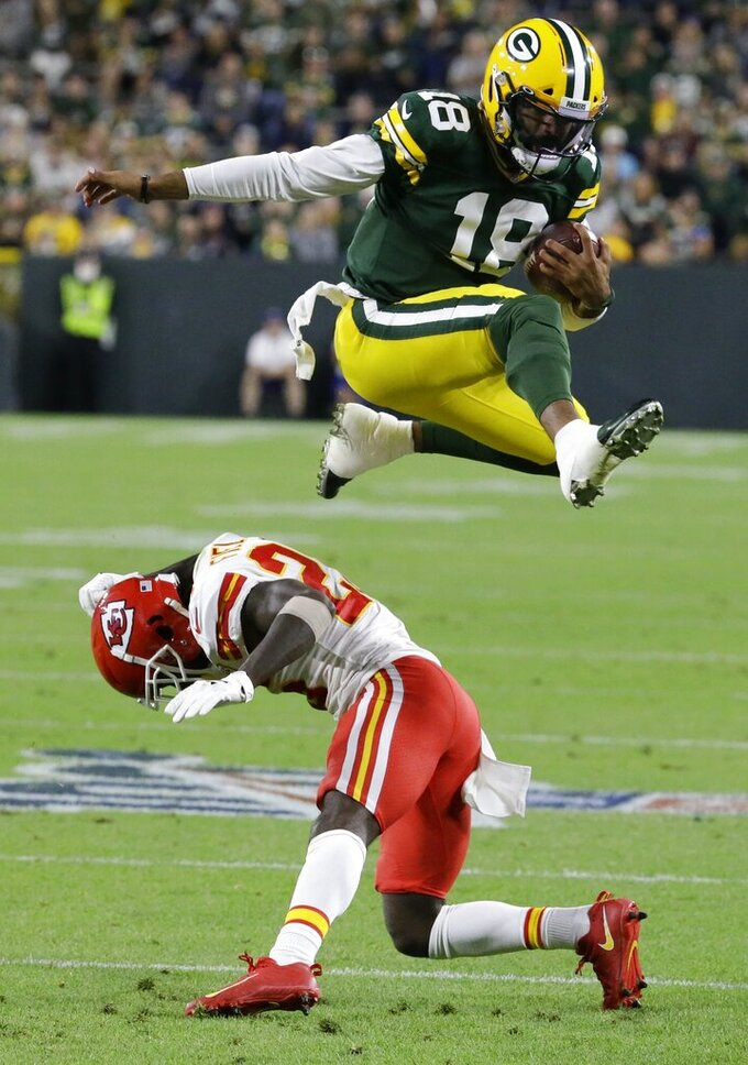 Green Bay Packers' Manny Wilkins leaps over Kansas City Chiefs' Mark Fields during the second half of a preseason NFL football game Thursday, Aug. 29, 2019, in Green Bay, Wis. (AP Photo/Mike Roemer)