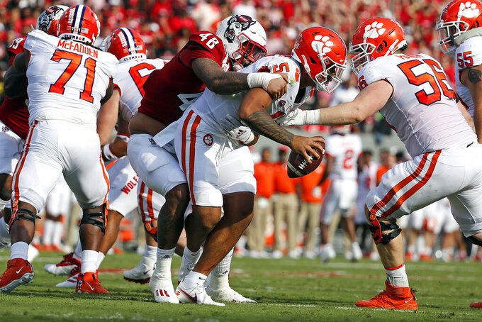 North Carolina State's Cory Durden (48) grabs a hold of Clemson's D.J. Uiagalelei (5) for a sack during the first half of an NCAA college football game in Raleigh, N.C., Saturday, Sept. 25, 2021. (AP Photo/Karl B DeBlaker)