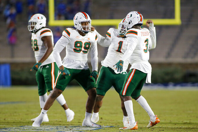 Miami defensive end Elijah Roberts (99), defensive lineman Nesta Jade Silvera (1) and linebacker Gilbert Frierson (3) celebrate after a fumble recovery against Duke during the second half of an NCAA college football game Saturday, Dec. 5, 2020, in Durham, N.C. (Nell Redmond/Pool Photo via AP)