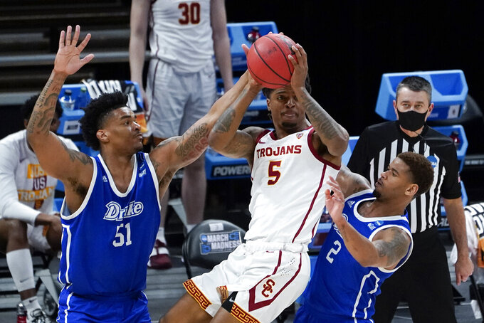 USC guard Isaiah White (5) pulls down a rebound from Drake forward Darnell Brodie (51) and Tremell Murphy (2) during the second half of a men's college basketball game in the first round of the NCAA tournament at Bankers Life Fieldhouse in Indianapolis, Saturday, March 20, 2021. (AP Photo/Paul Sancya)