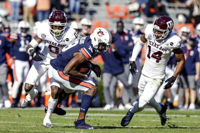 Auburn wide receiver Seth Williams (18) catches a pass as Texas A&M defensive back Keldrick Carper (14) and defensive back Myles Jones (0) defend during the first half of an NCAA college football game on Saturday, Dec. 5, 2020, in Auburn, Ala. (AP Photo/Butch Dill)