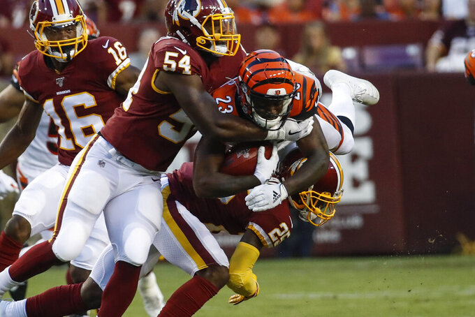Cincinnati Bengals' Darius Phillips (23) is hit by Washington Redskins' Myles Humphrey (54) and Jimmy Moreland (25) on a kickoff return during the first half of an NFL preseason football game Thursday, Aug. 15, 2019, in Landover, Md. (AP Photo/Alex Brandon)