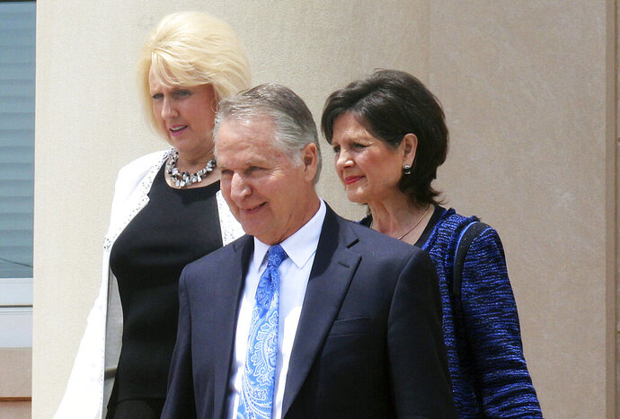 FILE - In this  July 2017, file photo, Kent Covington, front, his wife, Brooke, left, and a fellow member of the Word of Faith Fellowship church, Jayne Caulder, walk from the Rutherford County Courthouse in Rutherfordton, N.C., after a pretrial hearing for Brooke. Kent has been sentenced to 34 months in prison and ordered to pay more than $466,000 in restitution for his role in an unemployment fraud scheme involving businesses owned by church leaders. (Jean Gordon/Daily Courier via AP, File)
