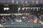 Fans take cover from the rain during the fourth inning of a baseball game between the New York Mets and the Toronto Blue Jays Wednesday, May 16, 2018, in New York. (AP Photo/Frank Franklin II)