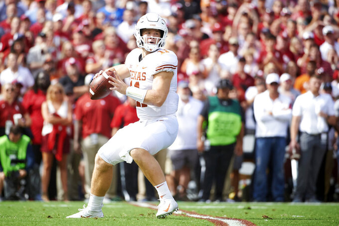 Texas quarterback Sam Ehlinger (11) drops back to pass against Oklahoma during the first half of an NCAA college football game at the Cotton Bowl, Saturday, Oct. 6, 2018, in Dallas. (AP Photo/Cooper Neill)