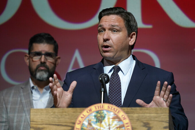 FILE - In this Tuesday, Sept. 14, 2021, file photo, Florida Gov. Ron DeSantis speaks at the Doral Academy Preparatory School in Doral, Fla. Florida filed suit against President Joe Biden's administration Tuesday, Sept. 28, 2021, claiming his immigration policy is illegal, and DeSantis signed an order barring state agencies from assisting with the relocation of undocumented immigrants arriving in the state. (AP Photo/Wilfredo Lee. File)