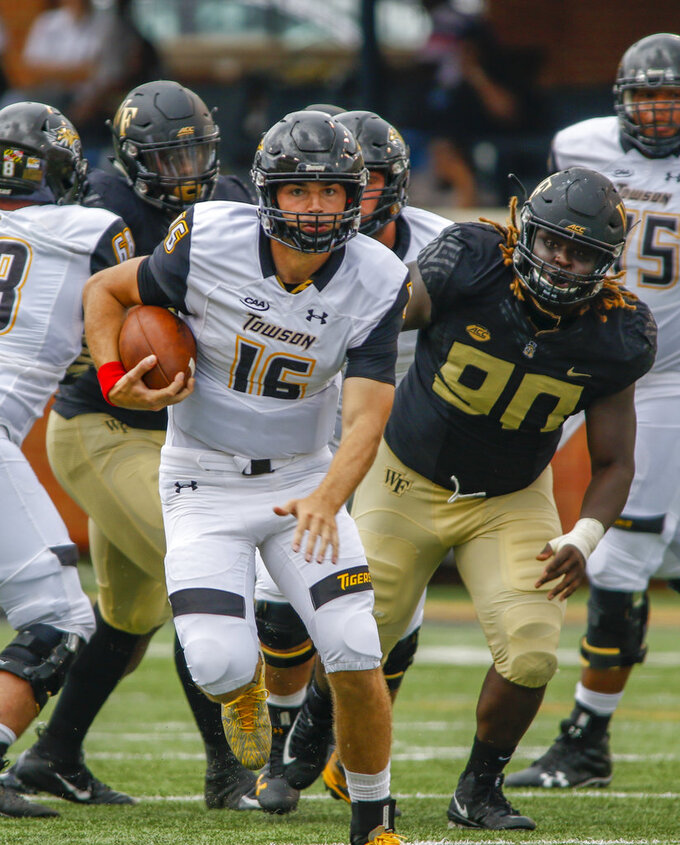 Towson quarterback Ryan Stover rushes for a first down ahead of Wake Forest defensive lineman Sulaiman Kamara (90) in the second half of an NCAA college football game in Winston-Salem, N.C., Saturday, Sept. 8, 2018. (AP Photo/Nell Redmond)