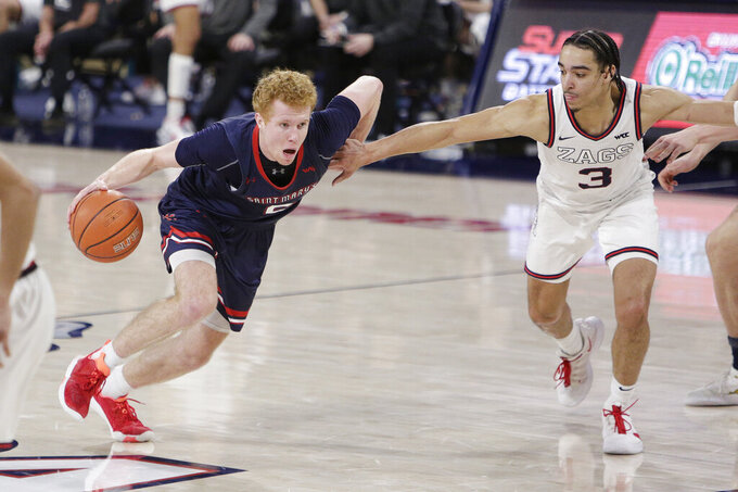 Saint Mary's guard Jabe Mullins, left, drives while pressured by Gonzaga guard Andrew Nembhard during the second half of an NCAA college basketball game in Spokane, Wash., Thursday, Feb. 18, 2021. (AP Photo/Young Kwak)