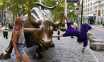 A man takes a playful leap while holding onto the Charging Bull statue in New York's financial district, Tuesday, Sept. 8, 2020. More sharp declines for big tech stocks are dragging Wall Street toward a third straight loss on Tuesday. (AP Photo/Mark Lennihan)