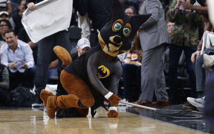 San Antonio Spurs mascot, The Coyote, uses a net as he dives for and catches a bat during the first half of an NBA basketball game between the San Antonio Spurs and the New Orleans Pelicans in San Antonio, Saturday, Feb. 2, 2019. (AP Photo/Eric Gay)