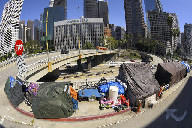 FILE - This May 21, 2020 file photo shows a homeless encampment at the corner of Wilshire Boulevard and Beaudry Avenue along the 110 Freeway during the coronavirus outbreak. in downtown Los Angeles. A judge has approved an agreement in which the city and county of Los Angeles will provide housing for almost 7,000 homeless people who live near freeways. Officials said Thursday, June 18, 2020 the city will provide 6,000 new beds within 10 months and another 700 beds over 18 months. Meanwhile the county will spend $300 million over five years to fund services for the people. (AP Photo/Mark J. Terrill, File)