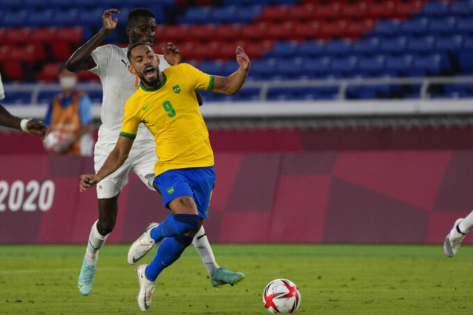 Brazil's Matheus Cunha, right, is fouled by Ivory Coast's Eboue Kouassi during a men's soccer match at the 2020 Summer Olympics, Sunday, July 25, 2021, in Yokohama, Japan. (AP Photo/Kiichiro Sato)