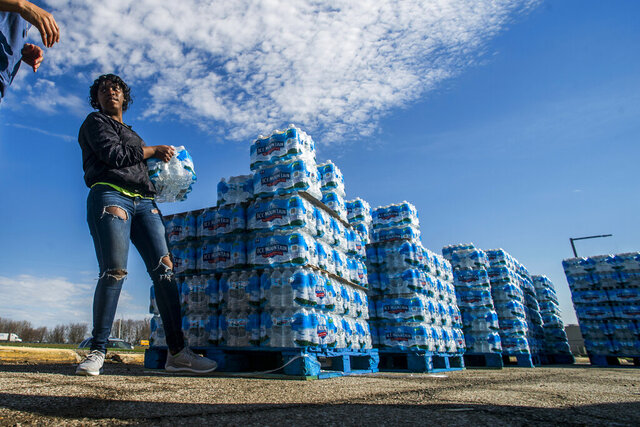 FILE - In this April 22, 2020 file photo volunteers load cases of water into vehicles in Flint, Mich. Flint's water scandal remains under criminal investigation, prosecutors said Friday, April, 17, 2020, pointing out a