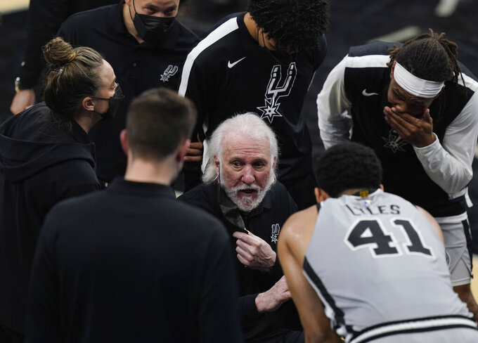 San Antonio Spurs head coach Gregg Popovich, center, talks with his team during the second half of an NBA basketball game against the Oklahoma City Thunder in San Antonio, Thursday, March 4, 2021. (AP Photo/Eric Gay)