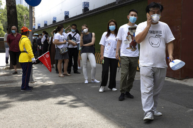 Residents wearing masks to curb the spread of the coronavirus line up for COVID-19 test outside the Worker's Stadium in Beijing on Tuesday, June 30, 2020. Test sites have sprung up through the Chinese capital as test have become a daily normal after the latest outbreak of the coronavirus, (AP Photo/Ng Han Guan)