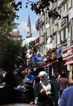 In this photo taken on Tuesday, Aug. 20, 2019, people walk in the Istanbul neighborhood of Aksaray, where many Syrians live. Syrians say Turkey has been detaining and forcing some Syrian refugees to return back to their country the past month. The expulsions reflect increasing anti-refugee sentiment in Turkey, which opened its doors to millions of Syrians fleeing their country's civil war. (AP Photo/Lefteris Pitarakis)