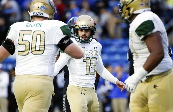 UAB place kicker Nick Vogel (19) is congratulated by offensive lineman David Galten (50) after Vogel kicked the winning 28-yard field goal against Middle Tennessee in the fourth quarter of the NCAA Conference USA championship college football game Saturday, Dec. 1, 2018, in Murfreesboro, Tenn. UAB won 27-25. (AP Photo/Mark Humphrey)