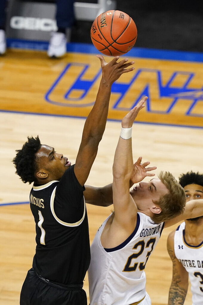 Wake Forest forward Isaiah Mucius (1) takes a shot as Notre Dame guard Dane Goodwin (23) defends during the half of an NCAA college basketball game in the first round of the Atlantic Coast Conference tournament in Greensboro, N.C., Tuesday, March 9, 2021. (AP Photo/Gerry Broome)
