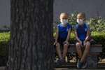 Children wearing masks to curb the spread of the coronavirus sit on a bench in Beijing, China on Monday, July 13, 2020. China reported only a handful of new cases of the virus, all of them brought from outside the country, as domestic community infections fall to near zero. (AP Photo/Ng Han Guan)