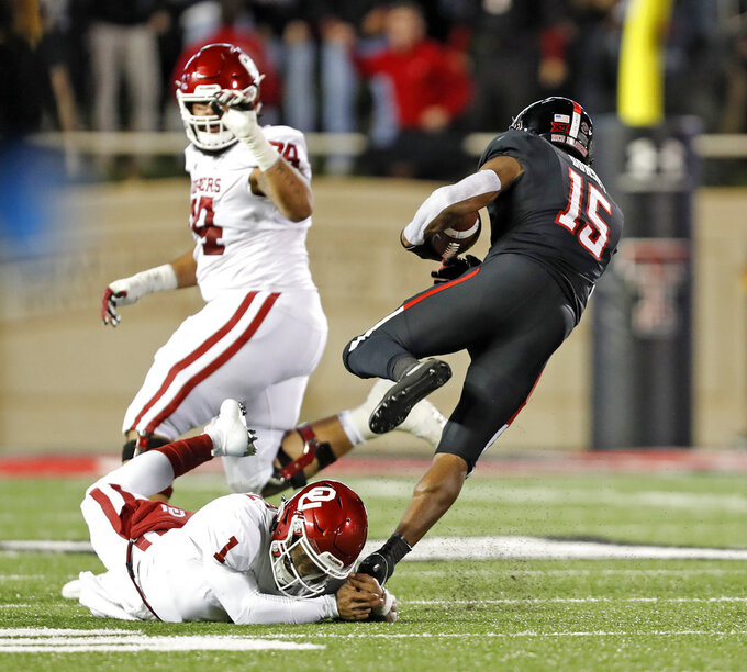 Texas Tech's Vaughnte Dorsey (15) breaks a tackle by Kyler Murray (1) after intercepting his pass during the first half of an NCAA college football game Saturday, Nov. 3, 2018, in Lubbock, Texas. (AP Photo/Brad Tollefson)
