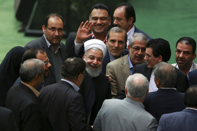 In this Monday, Feb. 4, 2019, photo, Iranian President Hassan Rouhani waves to media as he is surrounded by a group of lawmakers while he leaves the parliament after defending his proposed health minister, in Tehran, Iran. Lashed by criticism over his collapsing nuclear deal, Iran's President Rouhani faces an uncertain future amid a renewed hard-line effort to drive him from office years before his elected term ends. Iranian presidents typically see their popularity erode during their second four-year terms. But analysts say Rouhani is particularly vulnerable because of the economic crisis assailing the country's rial currency, which has hurt ordinary Iranians and emboldened critics to call for his ouster. (AP Photo/Vahid Salemi)
