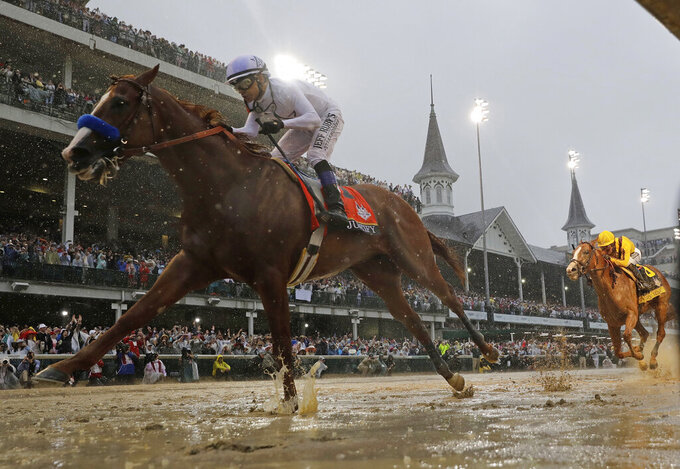 FILE - In this May 5, 2018, file photo, Mike Smith rides Justify to victory during the 144th running of the Kentucky Derby horse race at Churchill Downs in Louisville, Ky. The Run For The Roses is usually held on the first Saturday of May. Because of the pandemic, hold those mint juleps until Labor Day weekend, when the first leg of the Triple Crown is crammed into a slot that also marks the start of college football season. (AP Photo/Morry Gash, File)
