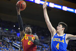 Southern California guard Jonah Mathews, left, shoots as UCLA guard Jaime Jaquez Jr. defends during the first half of an NCAA college basketball game Saturday, Jan. 11, 2020, in Los Angeles. (AP Photo/Mark J. Terrill)