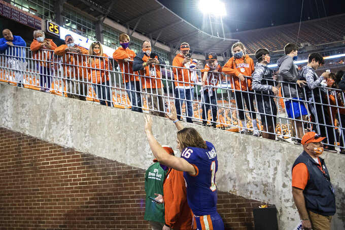 Clemson quarterback Trevor Lawrence (16) waves to fans as he leaves the team's home field for the last time, after the team's win over Pittsburgh in an NCAA college football game Saturday, Nov28, 2020, in Clemson, S.C. (Ken Ruinard/The Independent-Mail via AP, Pool)